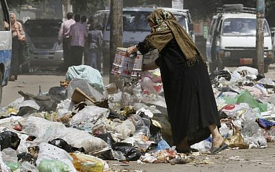 Illustrative photo of a woman in Cairo throwing her garbage into the street. (AP)