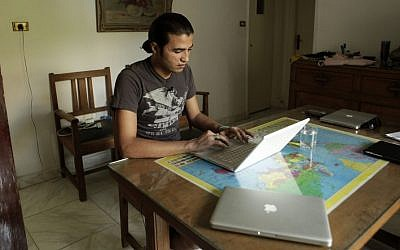 In this Tuesday, Aug. 28, 2012 photo, Mohammad B., a refugee from Daraa, Syria, looks at video from the day he was shot by Syrian government forces, in Cairo, Egypt. He fled Syria for his life in May 2011 after he was shot in the face and badly wounded in his hometown of Daraa, the birthplace of the uprising against Bashar Assad's rule. (AP Photo/Maya Alleruzzo)