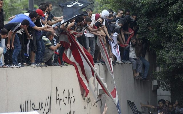 Protesters destroy an American flag at the US Embassy in Cairo and replace it with a black Islamic flag. They climbed the walls and were protesting a film they deemed offensive to Islam. (photo credit: Mohammed Abu Zaid, AP Photo)