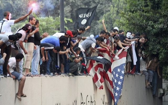 Protesters destroy an American flag pulled down from the US Embassy in Cairo, Egypt, September 11, 2012 (photo credit: AP/Mohammed Abu Zaid)
