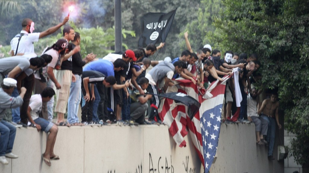 Protesters destroy an American flag pulled down from the US Embassy in Cairo, Egypt, Tuesday, September 11, 2012 (photo credit: AP/Mohammed Abu Zaid)