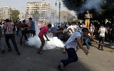 Egyptian protesters run for cover from tear gas during clashes near the US Embassy in Cairo earlier this month (photo credit: AP/Khalil Hamra)