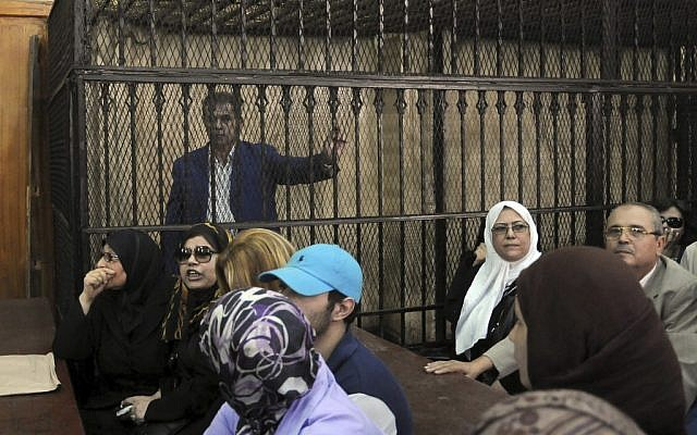 Tawfiq Okasha, a popular Egyptian TV presenter accused of inciting the killing of the country's new president on air, stands in the defendants cage at the opening of his trial, in Cairo, Egypt, on Saturday, Sept. 1 (photo credit: AP/Mohammed Assad)