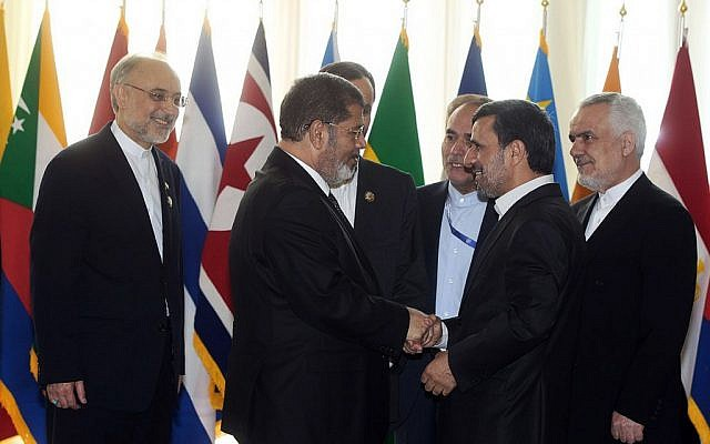 Egyotian President Mohammed Morsi (left) shakes hands with Mahmoud Ahmadinejad at the NAM conference in Tehran, August 30, 2012 (photo credit: AP)