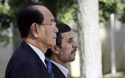 Iranian President Mahmoud Ahmadinejad, right, and president of the Presidium of North Korea's Supreme People's Assembly Kim Yong-nam, listen to their national anthems during an official welcoming ceremony in Tehran, Iran, Saturday. (photo credit: AP)