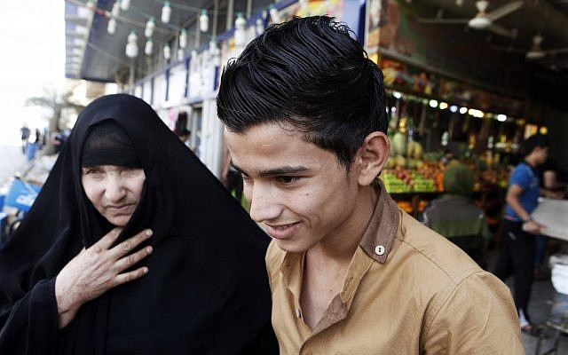 A mother with her young son shop at a market place in Kazimiyah neighborhood, northern Baghdad, Iraq, Sunday, Sept 2 (photo credit: AP/Karim Kadim)