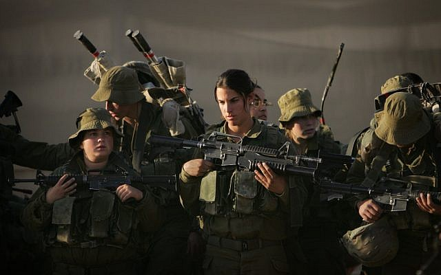 This file photo shows female soldiers preparing for a march near Ein Yahav in southern Israel in 2006 (photo credit: AP Photo/Oded Balilty, File)