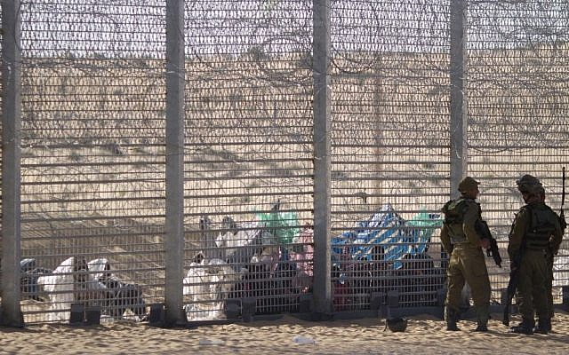 Israeli soldiers stand guard on Tuesday as Eritrean asylum seekers sit on the ground behind a border fence, after they attempted to cross illegally from Egypt into Israel. (photo credit: AP/Ariel Schalit)