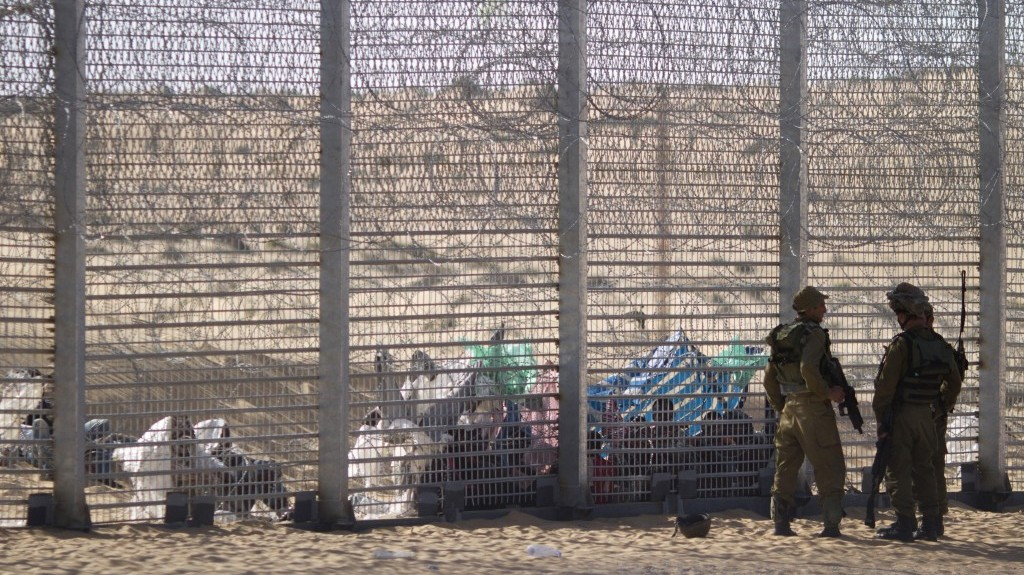 Israeli soldiers stand guard on Tuesday as Eritrean asylum-seekers sit on the ground behind a border fence, after they attempted to cross illegally from Egypt into Israel. (photo credit: AP/Ariel Schalit)