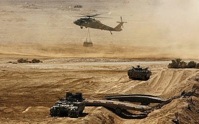 An Israeli helicopter flies above armored vehicles during an army exercise at the Shizafon Army Base in southern Israel. (photo credit: Tara Todras-Whitehill/AP)