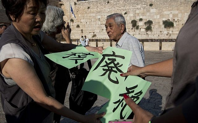 A Japanese group of survivors of the atomic bomb on Hiroshima during World War 2 hold signs calling for the abolition of Nuclear weapons at the Western Wall on September 10, 2012. (photo credit: Sebastian Scheiner/AP)