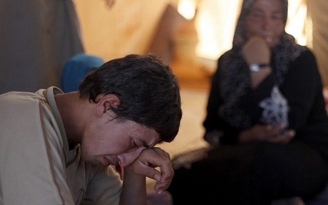 Basel Baradan, an 18-year-old farmer who fled his southern restive border town of Daraa, Syria with his family in July, wipes his eyes as he speaks during an interview at the Zaatari Refugee Camp, in Mafraq, Jordan. (photo credit: AP)