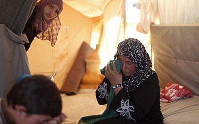 In this Tuesday, Sept. 11, 2012 photo, the 46-year-old wife of farmer Ghassan Baradan, who fled her southern restive border town of Daraa, Syria with her family in July, wipes her eyes as she speaks during an interview at the Zaatari Refugee Camp, in Mafraq, Jordan. (photo credit: AP)