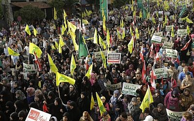 """Hezbollah supporters wave flags and hold up Arabic banners that read, """"At your service God's prophet; America equals terrorism; and America does not equal freedom,"""" during an anti-US rally in Beirut, Lebanon on Monday (photo credit: AP/Hussein Malla)"""