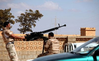 Libyan National Army soldiers in Benghazi prepare to enter Rafallah al-Sahati Islamic Militia Brigades compound, seen behind the wall. (photo credit: AP/Mohammad Hannon)