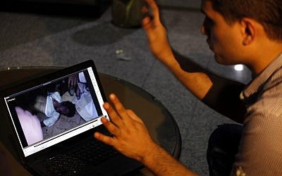 Fahd al-Bakoush, a freelance videographer, 22, shows a video he took of the body of U.S. Ambassador Chris Stevens being carried out of a small dark room in the U.S. consulate in Benghazi. (photo credit: AP/Mohammad Hannon)