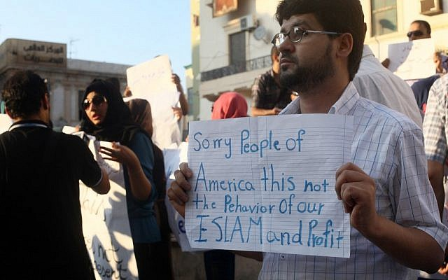 A Libyan man holds a placard in English during a demonstration on Wednesday, Sept. 12, 2012, against the attack on the US Consulate that killed four Americans, including the ambassador, in Benghazi, Libya. (photo credit: Ibrahim Alaguri/AP)