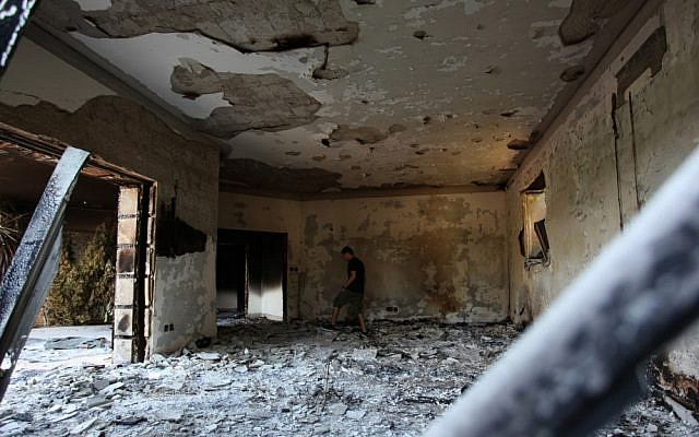 A Libyan man walks through the rubble of the damaged US Consulate in Benghazi after an attack that killed four Americans, including Ambassador Chris Stevens, on the night of Tuesday, September 11, 2012. (photo credit: AP/Mohammad Hannon)