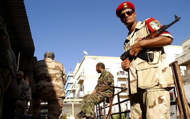 Libyan security forces stand guard as people turn in weapons in Benghazi, Libya, Saturday. (photo credit: AP)