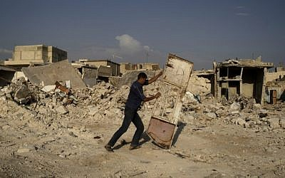 A Syrian man pushes a door away from the rubble of houses destroyed in a government airstrike in an outskirt of Aleppo on Friday (AP Photo/Muhammed Muheisen)