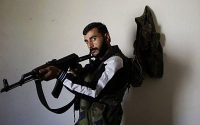 In this Wednesday, Sept. 5, 2012, photo, Syrian rebel fighter, Hamzah Alhassan, 25, a former blacksmith, poses for a picture at a house where he and others wait their turn to go and fight against government forces in Aleppo. (AP Photo/Muhammed Muheisen)