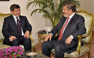 Egyptian President Mohammed Morsi, right, meets with Turkish Foreign Minister Ahmet Davutoglu at the Presidential Palace in Cairo, Egypt on Monday. (photo credit: AP/Egyptian Presidency)