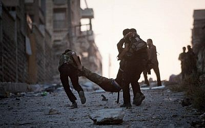 FSA soldiers drag a severely wounded colleague after he was allegedly shot by a Syrian Army sniper in Aleppo, Syria, on Saturday. (photo credit: Manu Brabo/AP)