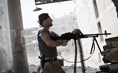A Free Syrian Army fighter fires at Syrian Army positions (photo credit: AP/Manu Brabo)