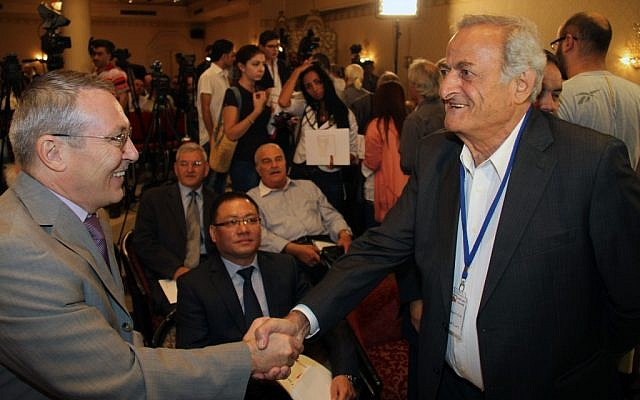 Syrian opposition members shake hands in a rare meeting in Damascus, September 23 (photo credit: AP/Bassem Tellawi)