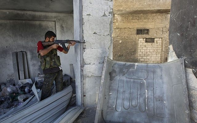 A Free Syrian Army Soldier takes his position in Aleppo, September 24 (photo credit: AP/Hussein Malla)