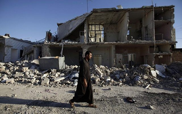 A Syrian man walks by a house destroyed in a Syrian government bombing in Azaz, near Aleppo, August 24, 2012 (photo credit: AP/Muhammed Muheisen)
