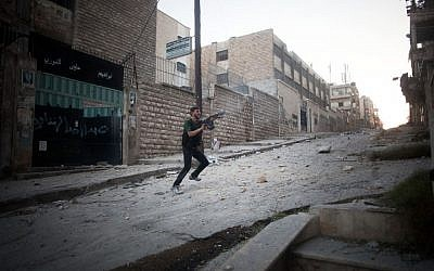 A opposition soldier fires towards Syrian Army positions in Aleppo, Syria, on Saturday September 8 2012 (photo credit: AP/Manu Brabo)