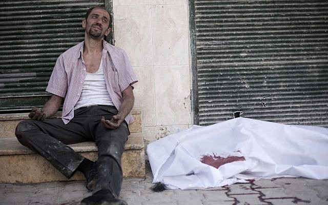 A man cries near the body of his brother, killed by a Syrian Army sniper, in Aleppo on Thursday (photo credit: AP/Manu Brabo)