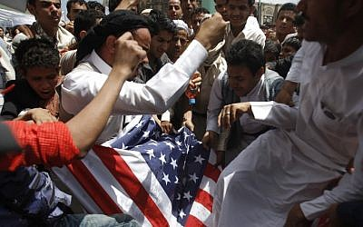 Protesters destroy an American flag pulled down during clashes with police near the U.S. Embassy in Sanaa, Yemen, Friday, Sept. 14, 2012, as part of widespread anger across the Muslim world about a film ridiculing Islam's Prophet Muhammad. (AP Photo/Hani Mohammed)