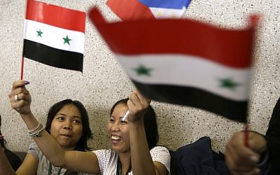 Overseas Filipino Workers, who fled the civil war in Syria, wave Syrian and Philippine flags upon arriving at the Ninoy Aquino International Airport in Manila via a chartered flight by the International Organization for Migration on Tuesday, September 11, 2012 (Photo credit: AP/Bullit Marquez)