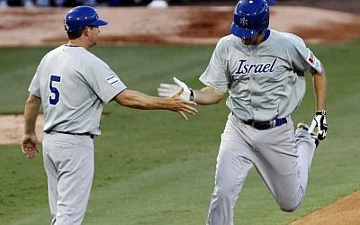 Israel's Nate Freiman, right, is congratulated by third base coach Mark Loretta after hitting a home run against South Africa in the first inning of a World Baseball Classic qualifier baseball game in Jupiter, Florida, on Wednesday. (photo credit: AP Photo/Alan Diaz)