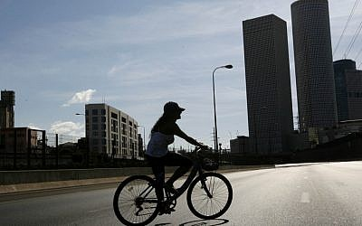 A young woman riding her bicycle by the Azrieli Center near the Ayalon Highway in Tel Aviv on Yom Kippur, when the road is car free. (photo credit: Miriam Alster/Flash90/JTA)