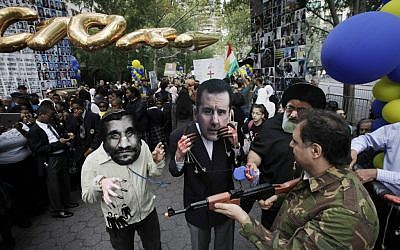 Men wearing masks of Iranian President Mahmoud Ahmadinejad, left, Syrian President Bashar Assad, center, and Iranian Ayatollah Ali Khamenei are joined by a man in military garb carrying a toy gun during a protest led by Iranian Americans and Syrian Americans outside the United Nations on September 26 in New York. (photo credit: AP/Mark Lennihan)