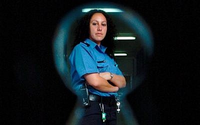 A female prison guard poses for the camera through a keyhole in an Israeli jail (photo credit: Nati Shohat/Flash90)