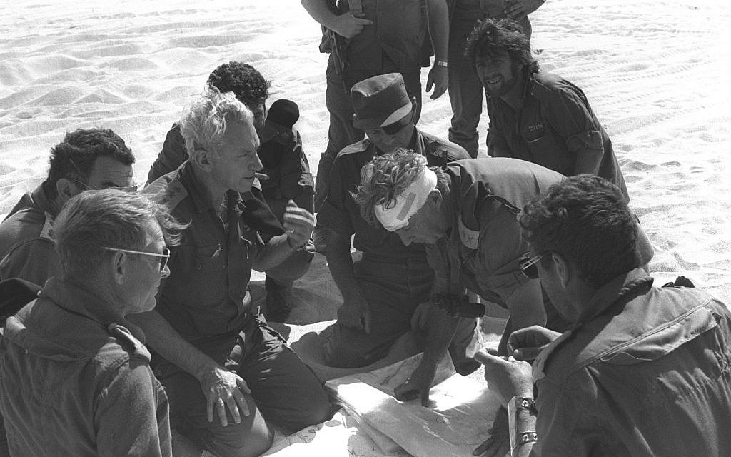 Former chief of staff Haim Bar-Lev, center left, consults with Maj. Gen. Ariel Sharon (with bandage) and Moshe Dayan, center, during the 1973 Yom Kippur War. (photo credit: GPO/Flash90)