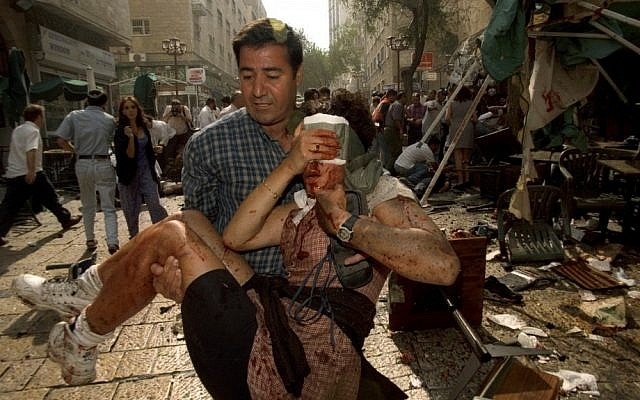 An Israeli man carries an injured woman from the scene of a triple Palestinian suicide bombing in Jerusalem on September 4, 1997. (photo credit: Flash90)