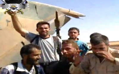 Syrian rebels in front of a downed Syrian warplane (photo credit: Image capture YouTube)