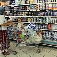 Illustrative: A woman shops with her son at the Rami Levy supermarket in the Gush Etzion settlement bloc. (Nati Shohat/Flash90)