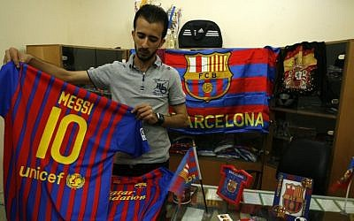 A Palestinian vendor stands among flags and shirts of Barcelona's football team at a sporting goods store in Rafah, in the southern Gaza strip, on September 29 (photo credit: Abed Rahim Khatib/Flash90)
