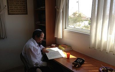 Rabbi Yair Frank, using his last moments in Migron to study Talmud (Photo credit: Mitch Ginsburg/ Times of Israel)