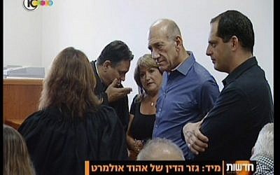 Ehud Olmert in blue, and his assistant Shula Zaken, facing camera, speaking to their lawyers before the sentencing Monday. (Screenshot/Channel 10)
