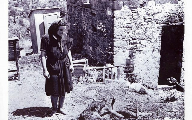 A woman examines the wreckage left behind by soldiers of the Hermann Goering division following a reprisal massacre in the Italian town of San Pancrazio in July 1944 (photo credit: National Archives of Canada)