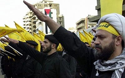 Hezbollah fighters take an oath during a parade to continue the path of resistance against Israel. (photo credit: AP/Hussein Malla)