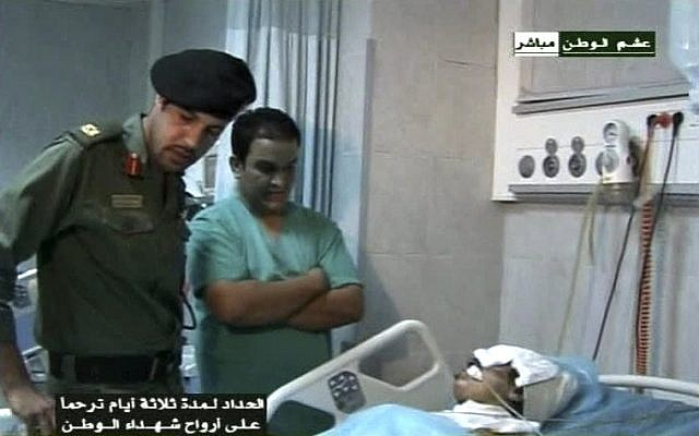 This video image broadcast Wednesday Aug. 10, 2011 by Libyan TV purports to shows Moammar Gadaffi's youngest son Khamis, left,  visiting an injured man in a hospital in Tripoli, Libya on Tuesday Aug. 9, 2011 (photo credit: AP/LIbyan TV)