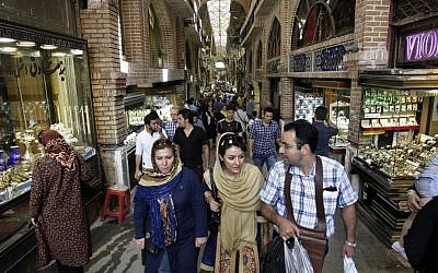 Iranians make there way through Tehran's old main bazaar in July (photo credit: AP/Vahid Salemi)